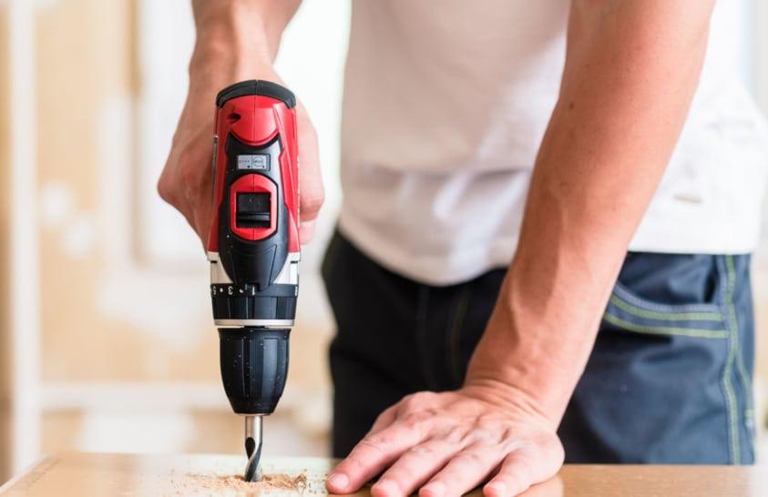 xicot practicant bricolatge amb un trepant elèctric i una fusta