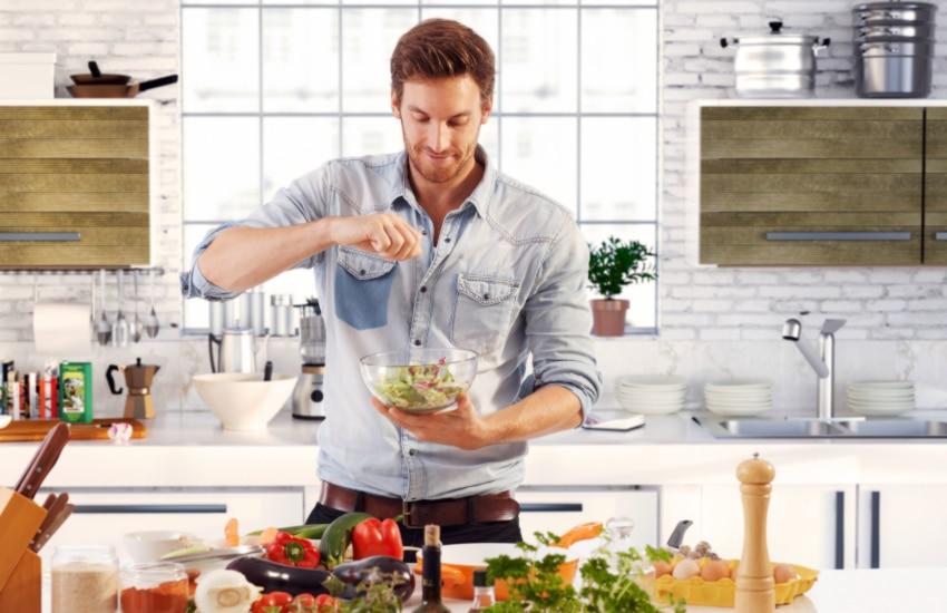chico preparando una ensalada con muchos ingredientes en lo alto de la mesa